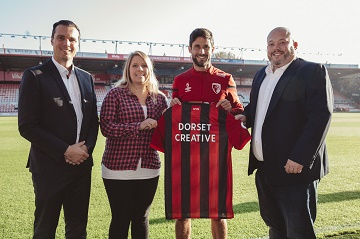 A commemorative Cherries shirt is presented by AFC Bournemouth Commercial Director Rob Mitchell, left, and midfielder Andrew Surman to Dorset Creative co-founders Rowena and Nathan Revill to welcome the firm as a partner of the club