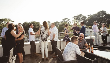 Guests at the AFC Business Al Fresco Evening enjoy the sunshine on the balcony of Bubbles Champagne Lounge at the club